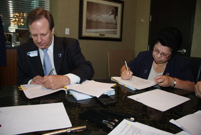 Jack Levine and Maria Brackett sign merger documents